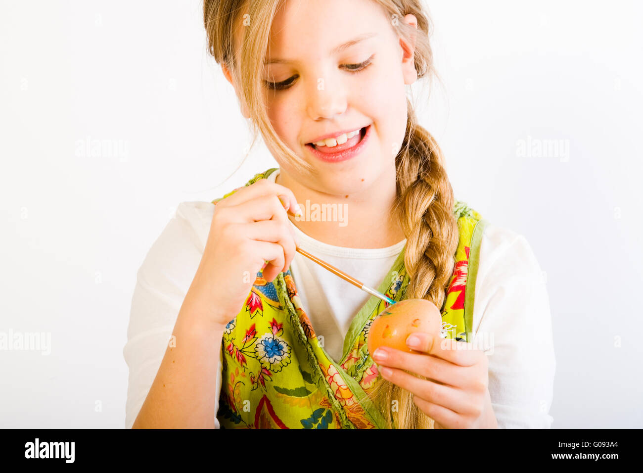 Young girl having fun painting eggs for easter - Stock Image