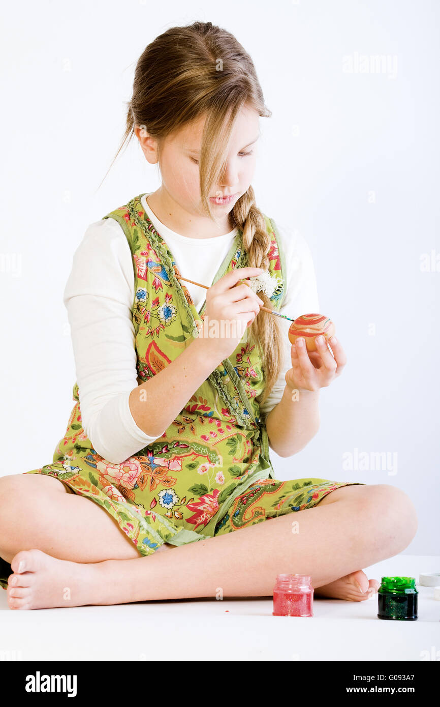 Young girl concentrated on painting eggs for easter - Stock Image
