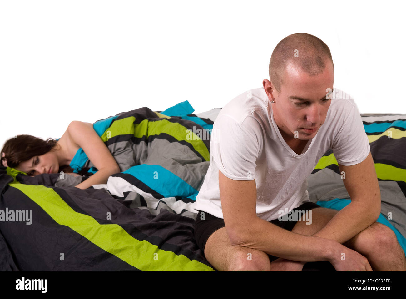 Young worried couple in bed with relation problems - Stock Image