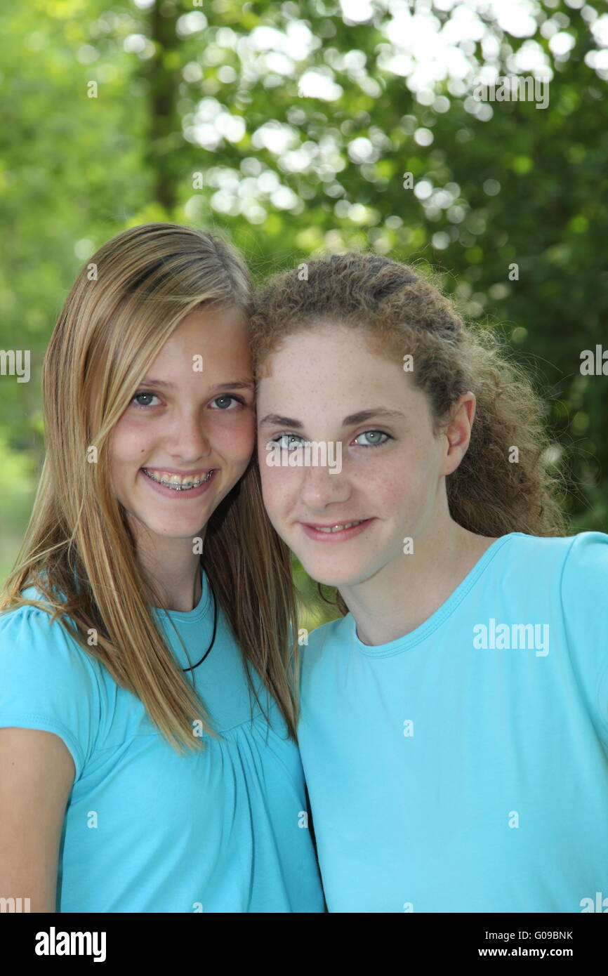 Two teenage girls smiling while posing together - Stock Image