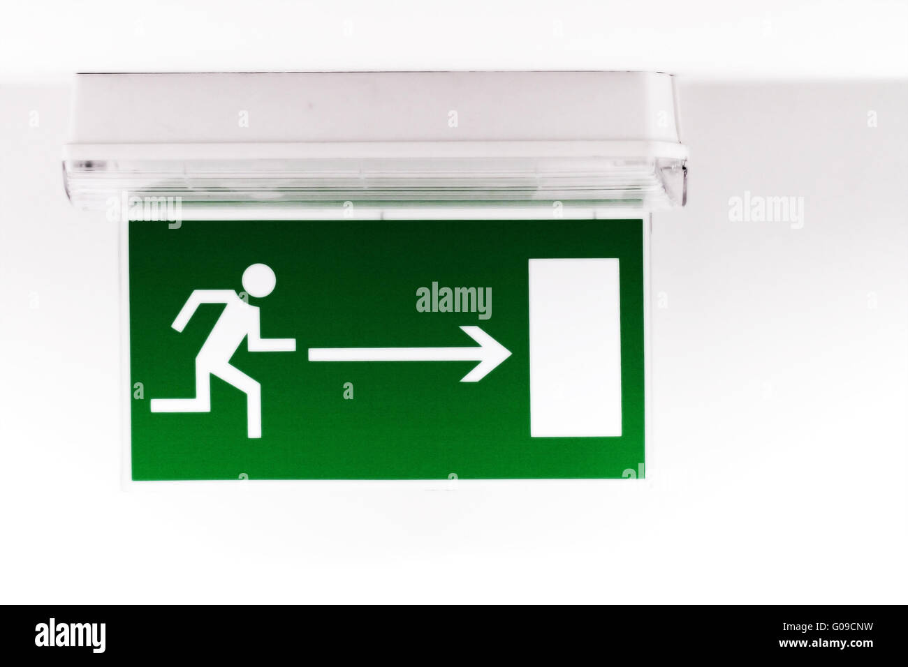 Emergency exit sign in a building glowing green - Stock Image
