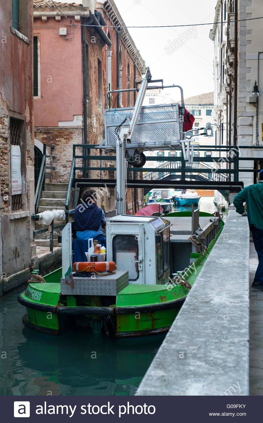 Refuse collection barge at work, Venice, Italy, April - Stock Image
