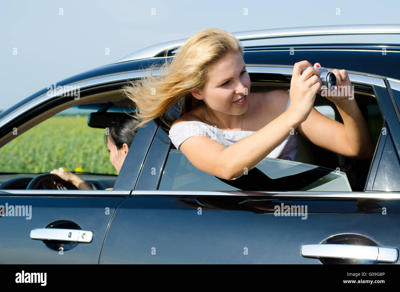 Attractive woman photographing from car window - Stock Image