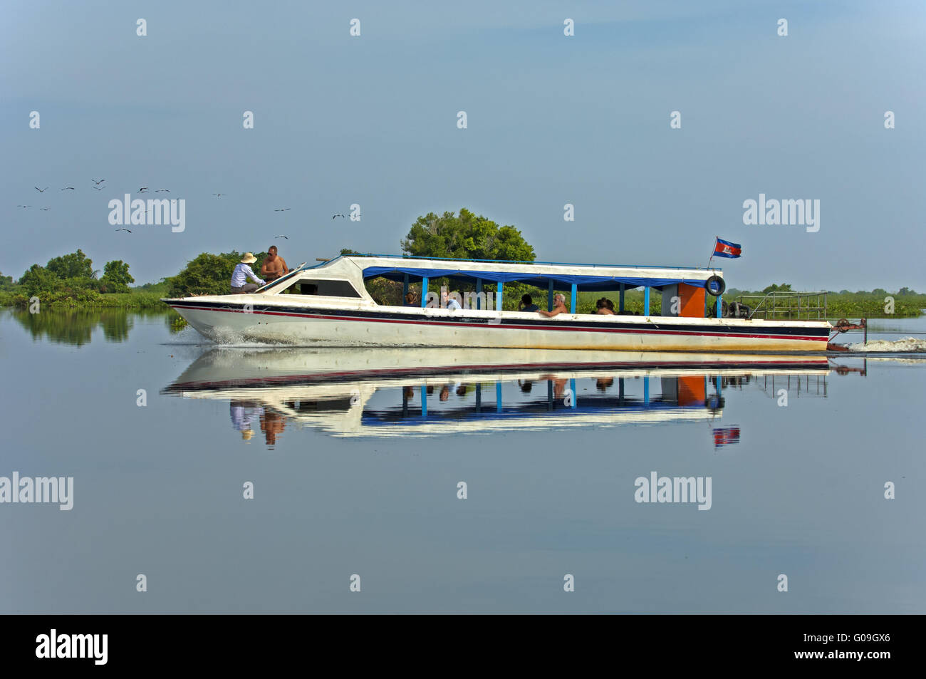 Excursion ship mirrored in the Tonle Sap Lake Stock Photo
