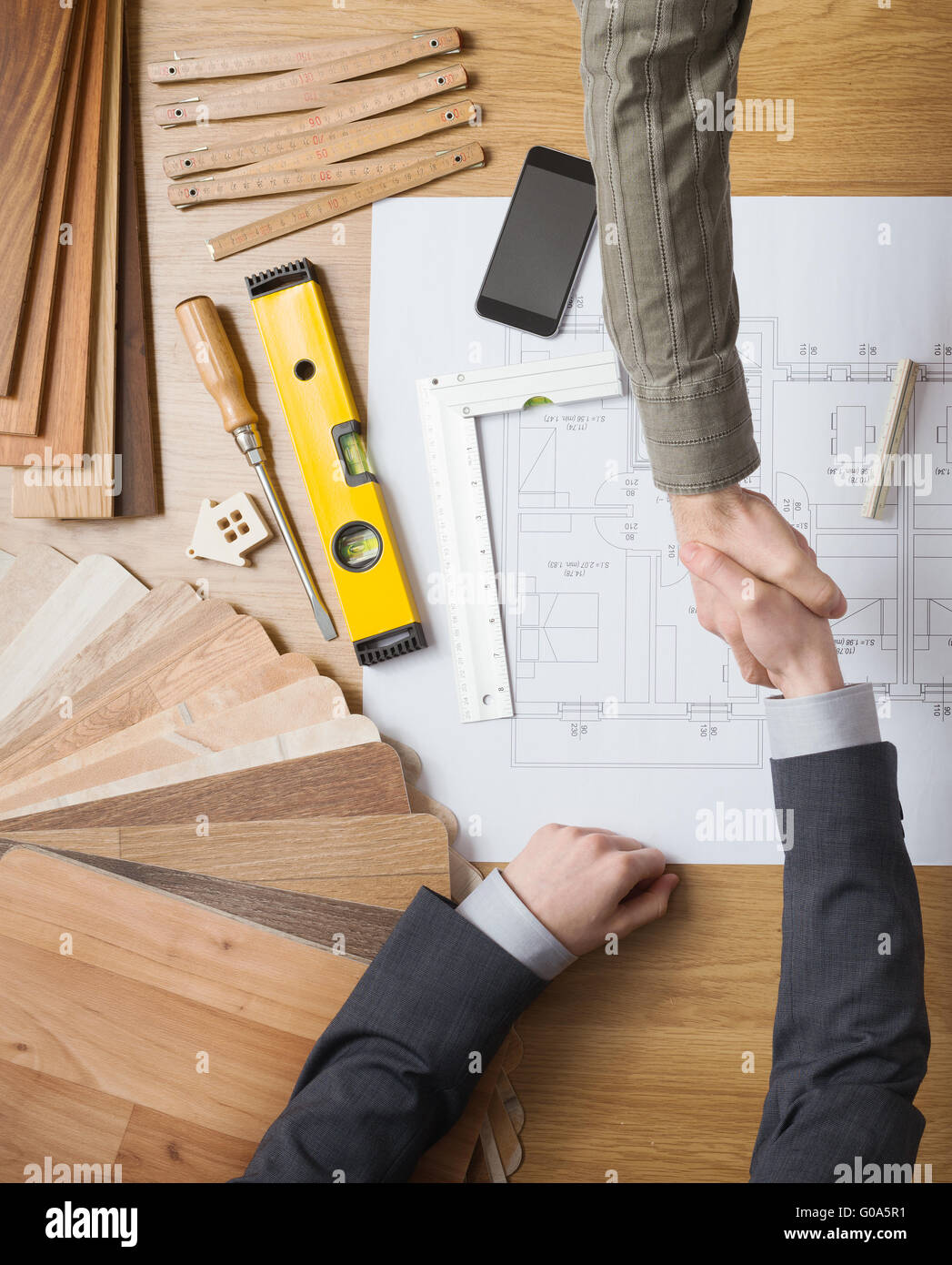 Customer businessman and construction engineer working together on a building project, they are shaking hands, desktop - Stock Image