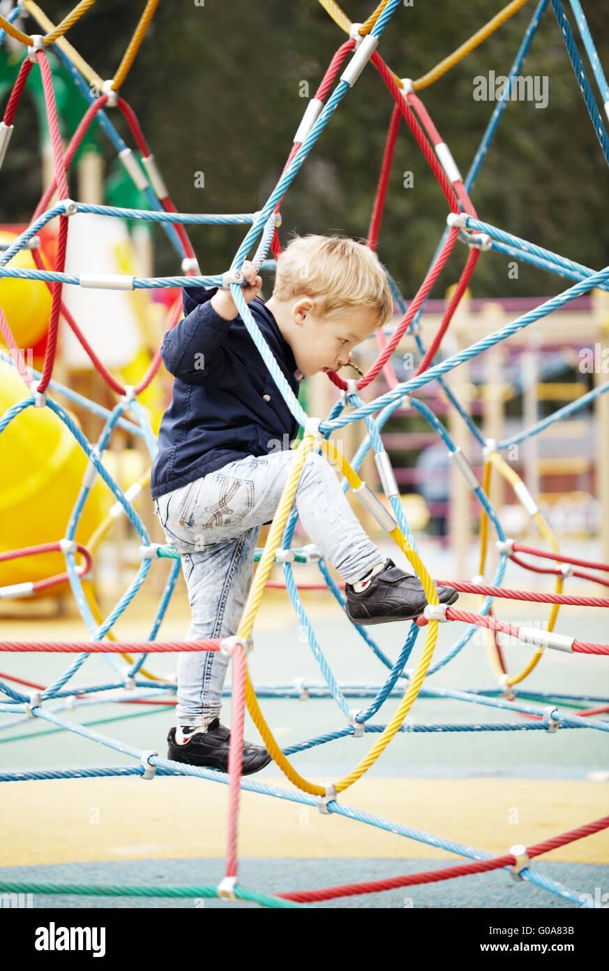 Happy little boy climbing on playground equipment - Stock Image