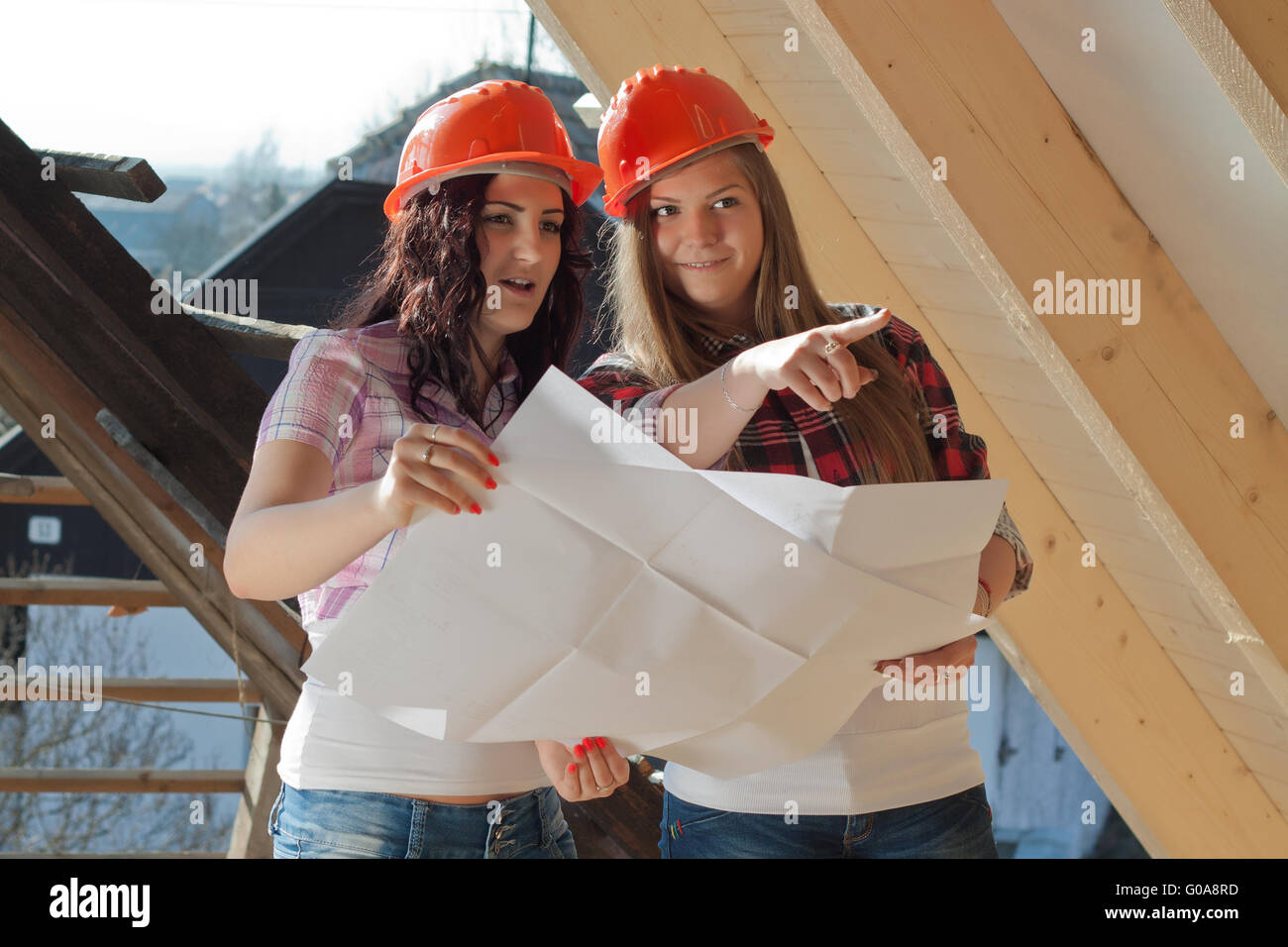 Two young women workers on the roof - Stock Image