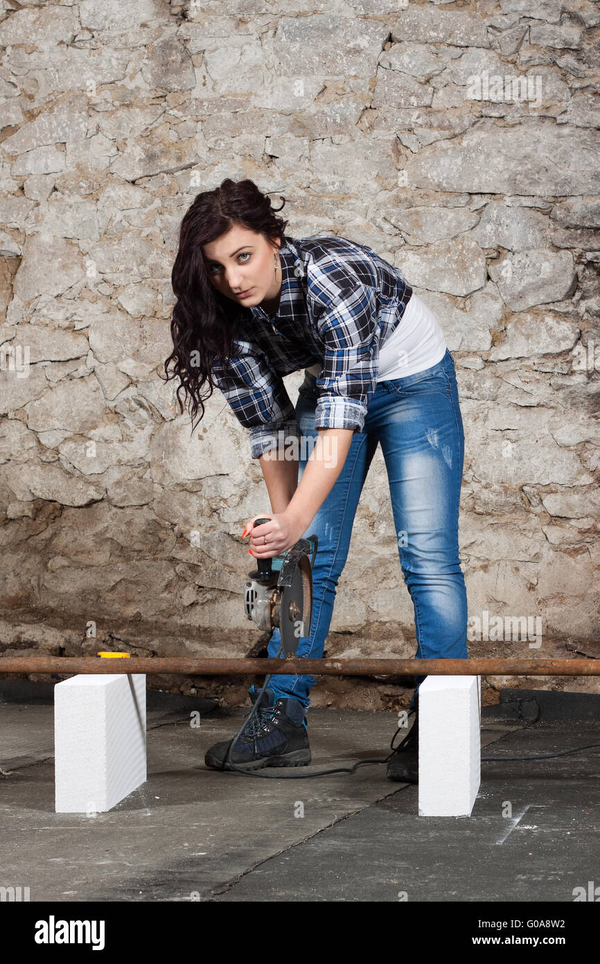Young long-haired woman with an angle grinder - Stock Image