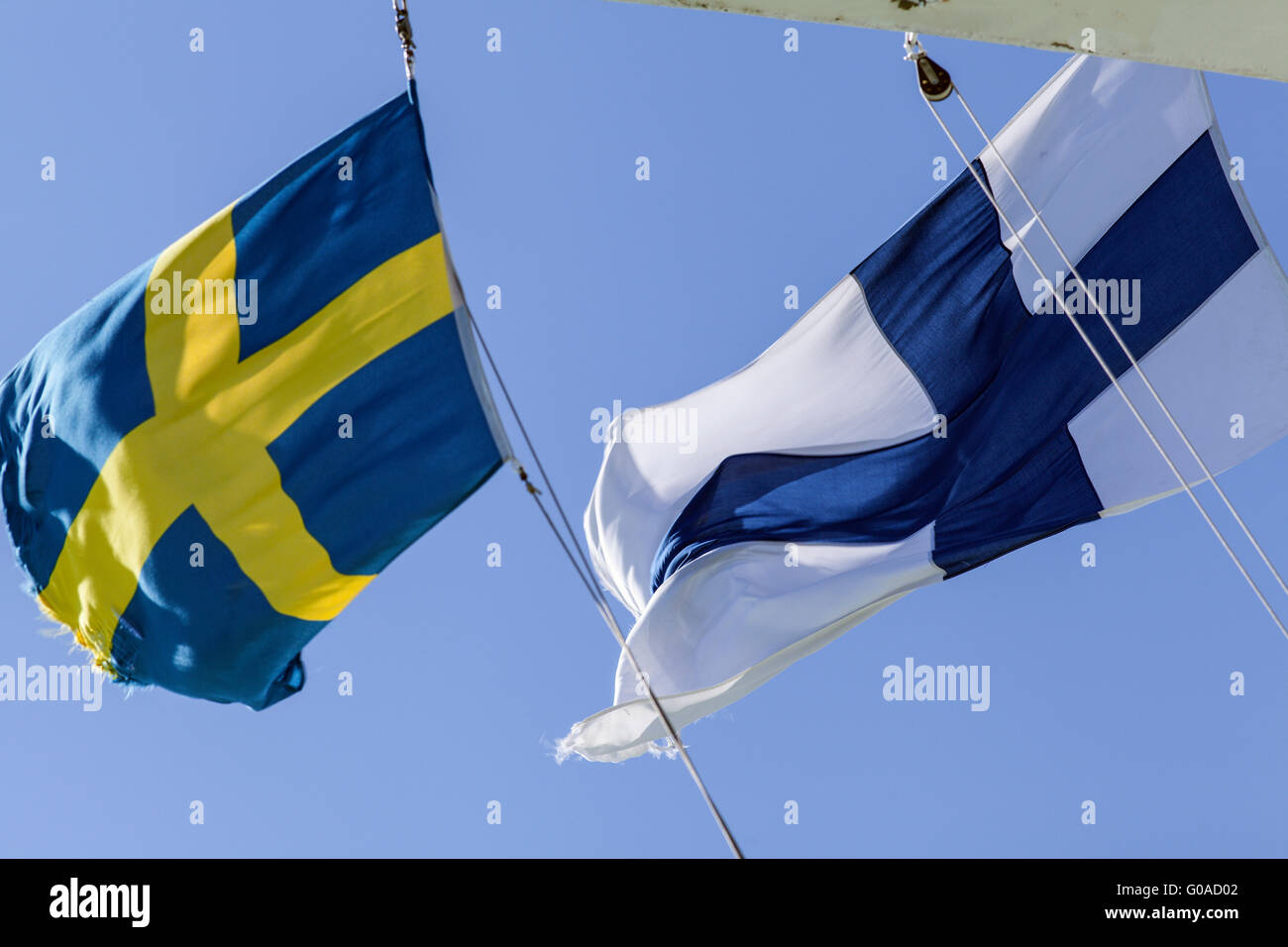 Finland, Sweden, Finnish, Swedish Standards. White, blue and yellow. On top of a ship. Strong wind, sunny. Stock Photo