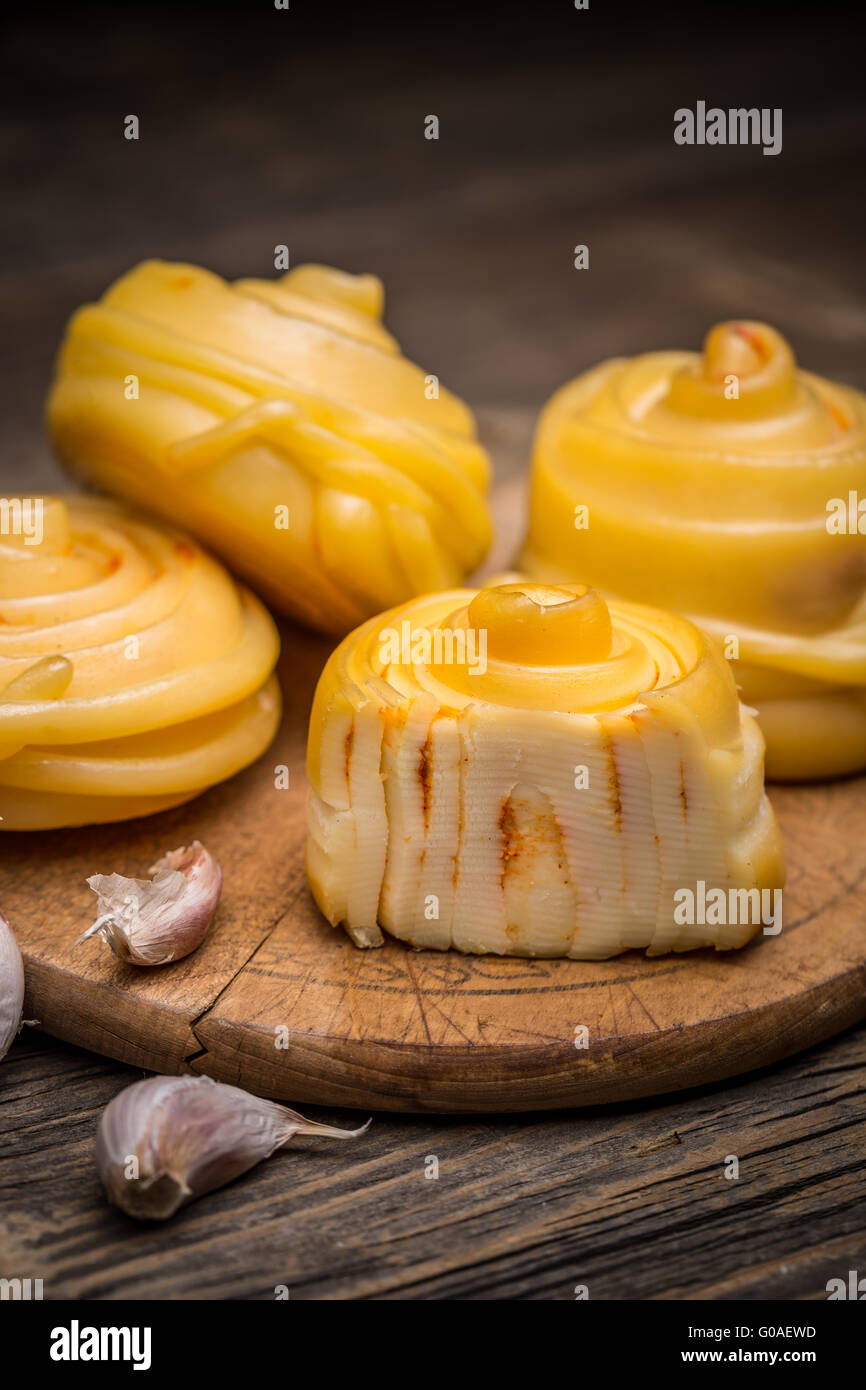 Twisted handicraft cheese on wooden board - Stock Image