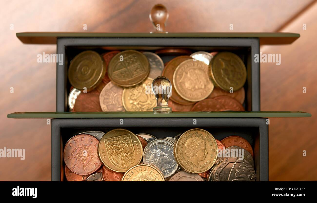 Stash of Coins kept in jewelry draws home savings concept. - Stock Image