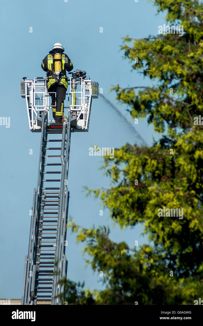 fireman with helmet on the big ladder is clearing - Stock Image