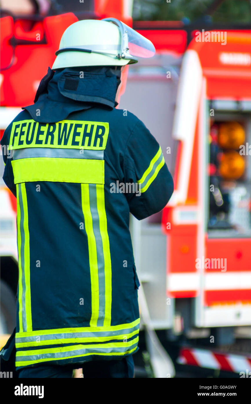back of a fire fighter with helmet in front of his - Stock Image