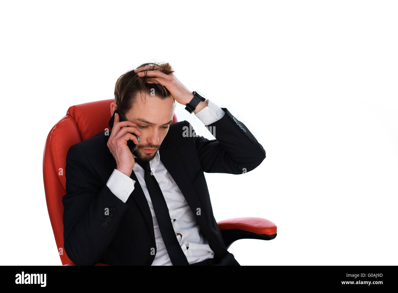 Worried businessman chatting on his mobile - Stock Image