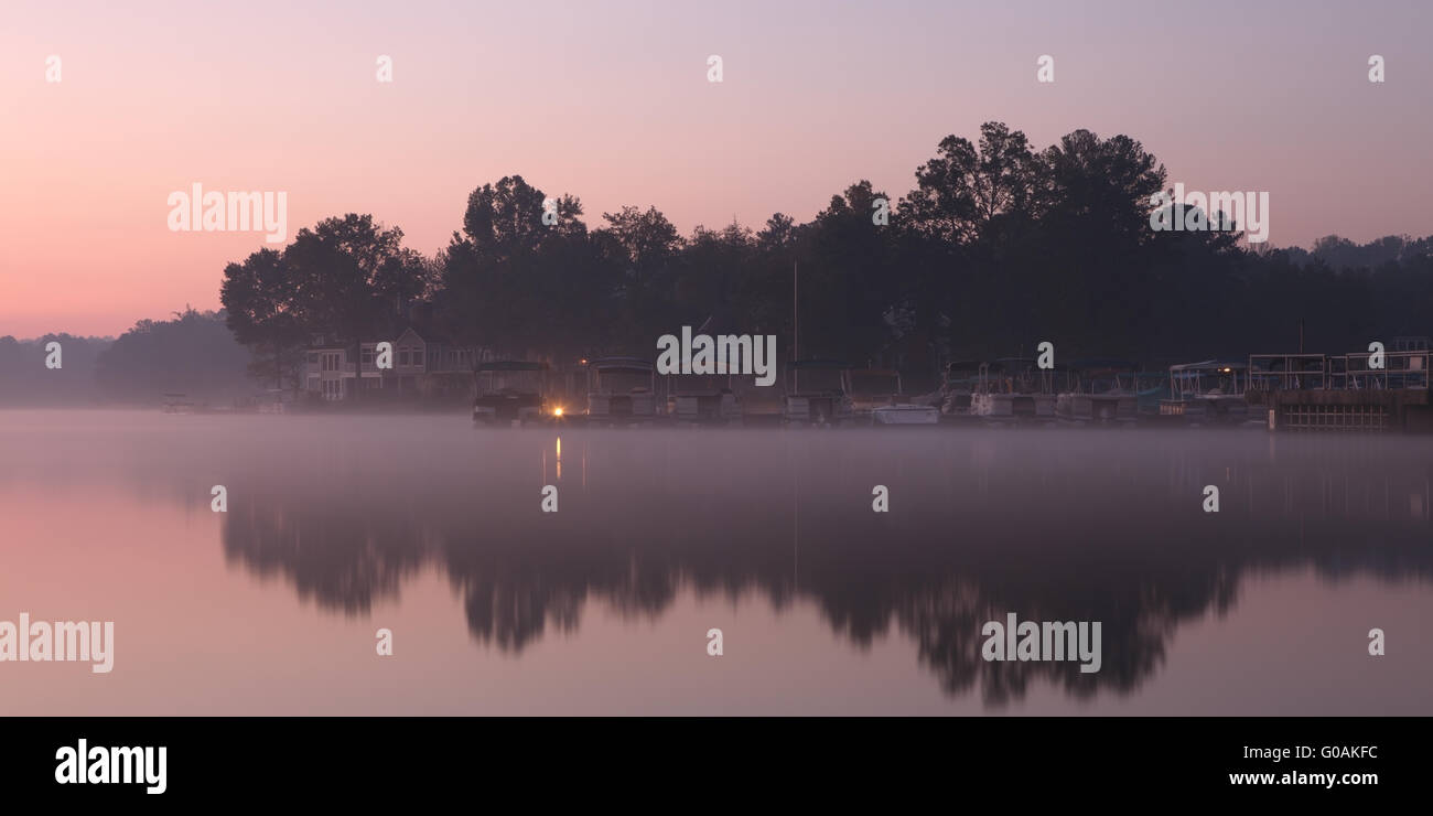 Misty morning at the lake with houses and jetty - Stock Image