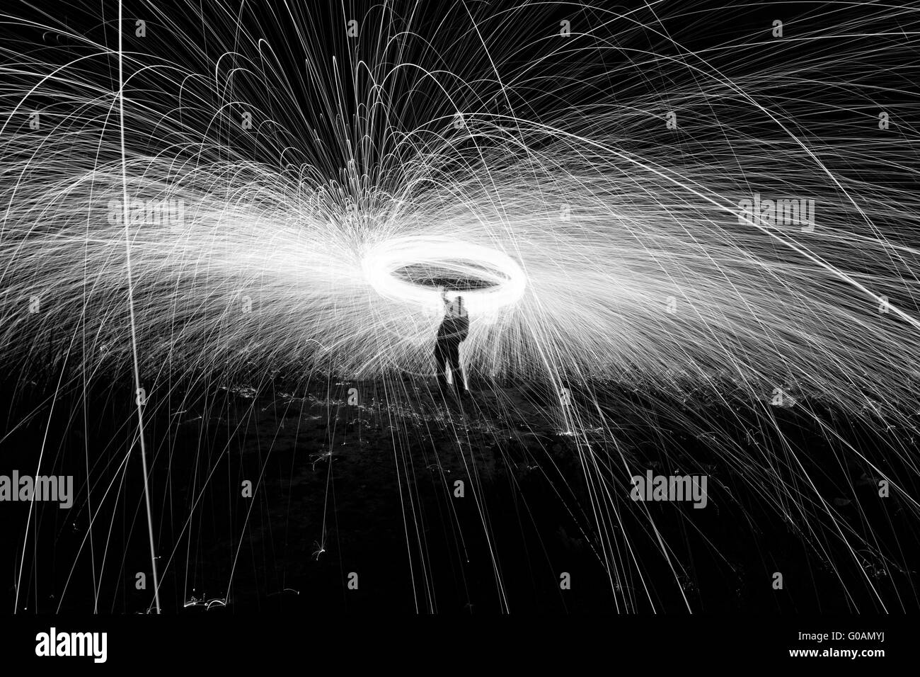 Showers of hot glowing sparks from spinning steel wool. - Stock Image