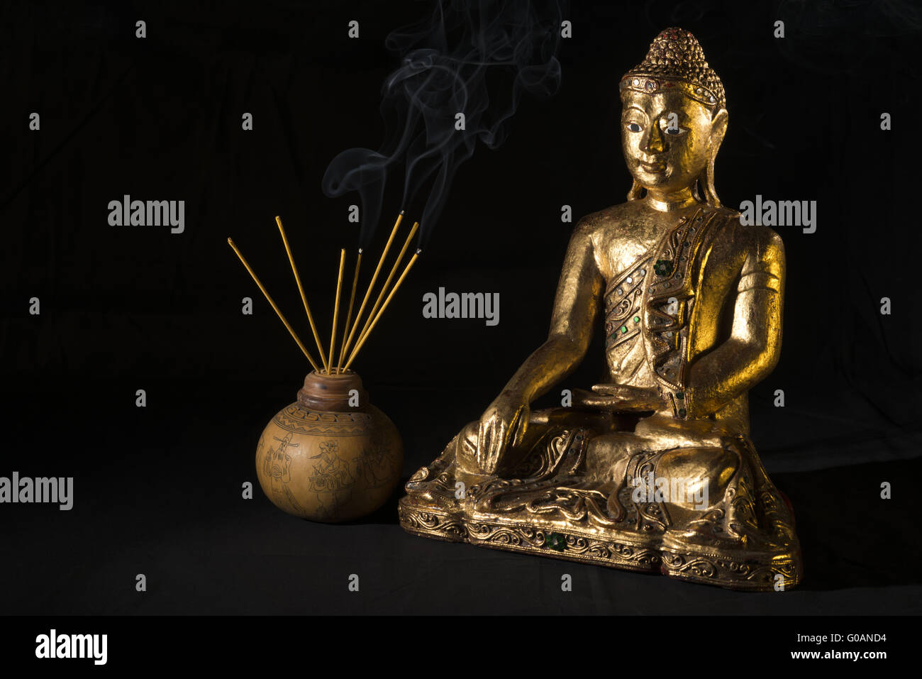 Buddah with incense sticks Stock Photo