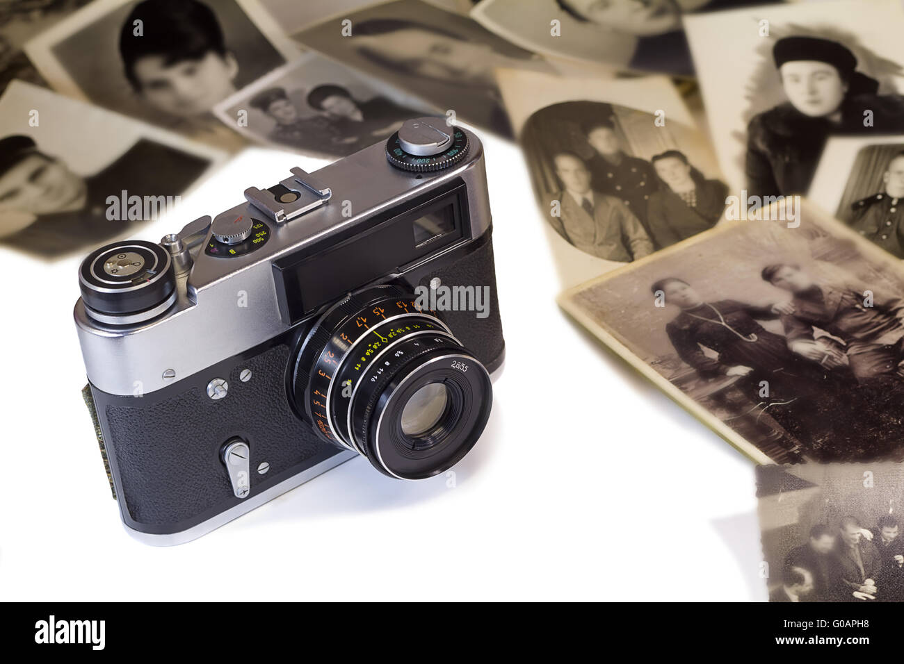 The old film camera and ancient photos on a white - Stock Image