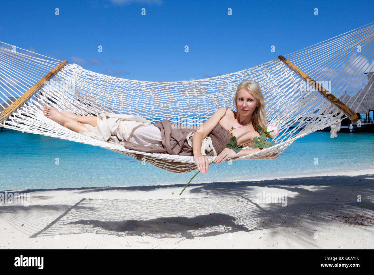 woman in a long sundress in a hammock on a sea bac - Stock Image
