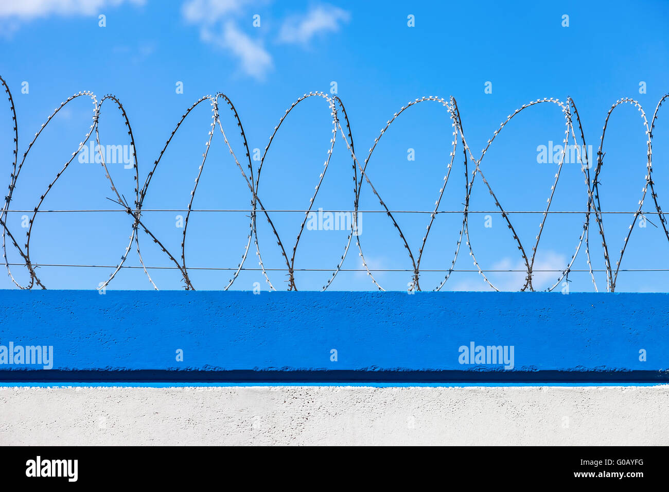 Barbed wire on the fence against a blue sky background - Stock Image