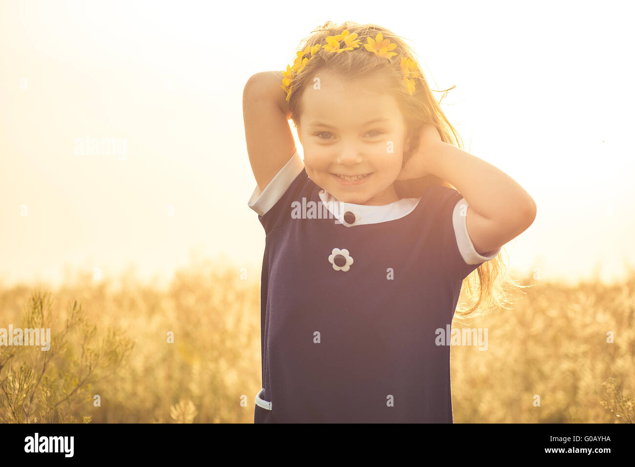 the beautiful little girl in a blue dress laughs Stock Photo