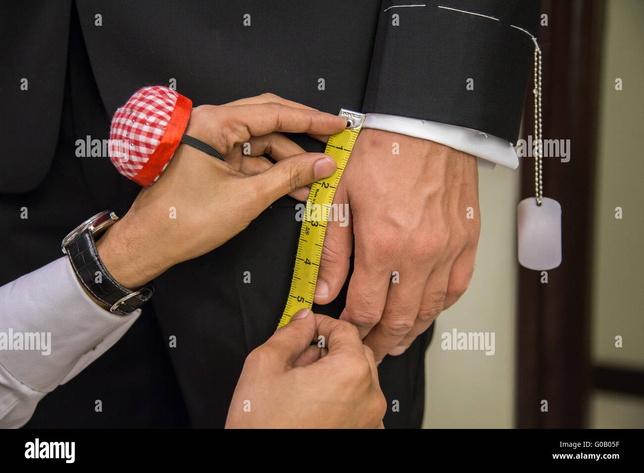 Tailor is measuring a hand of a client - Stock Image