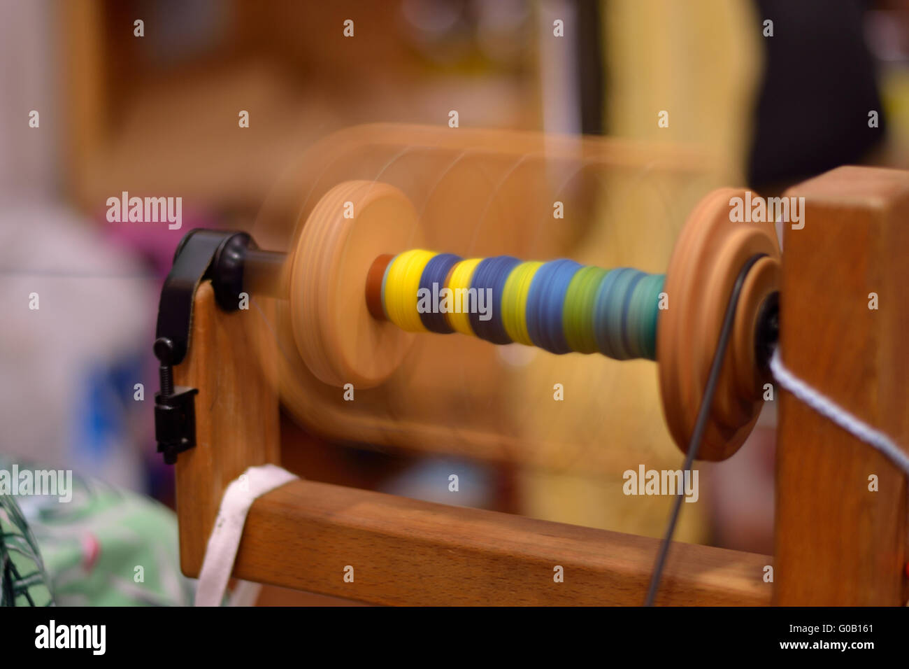 Spinning wheel spool rotates with colored wool - Stock Image