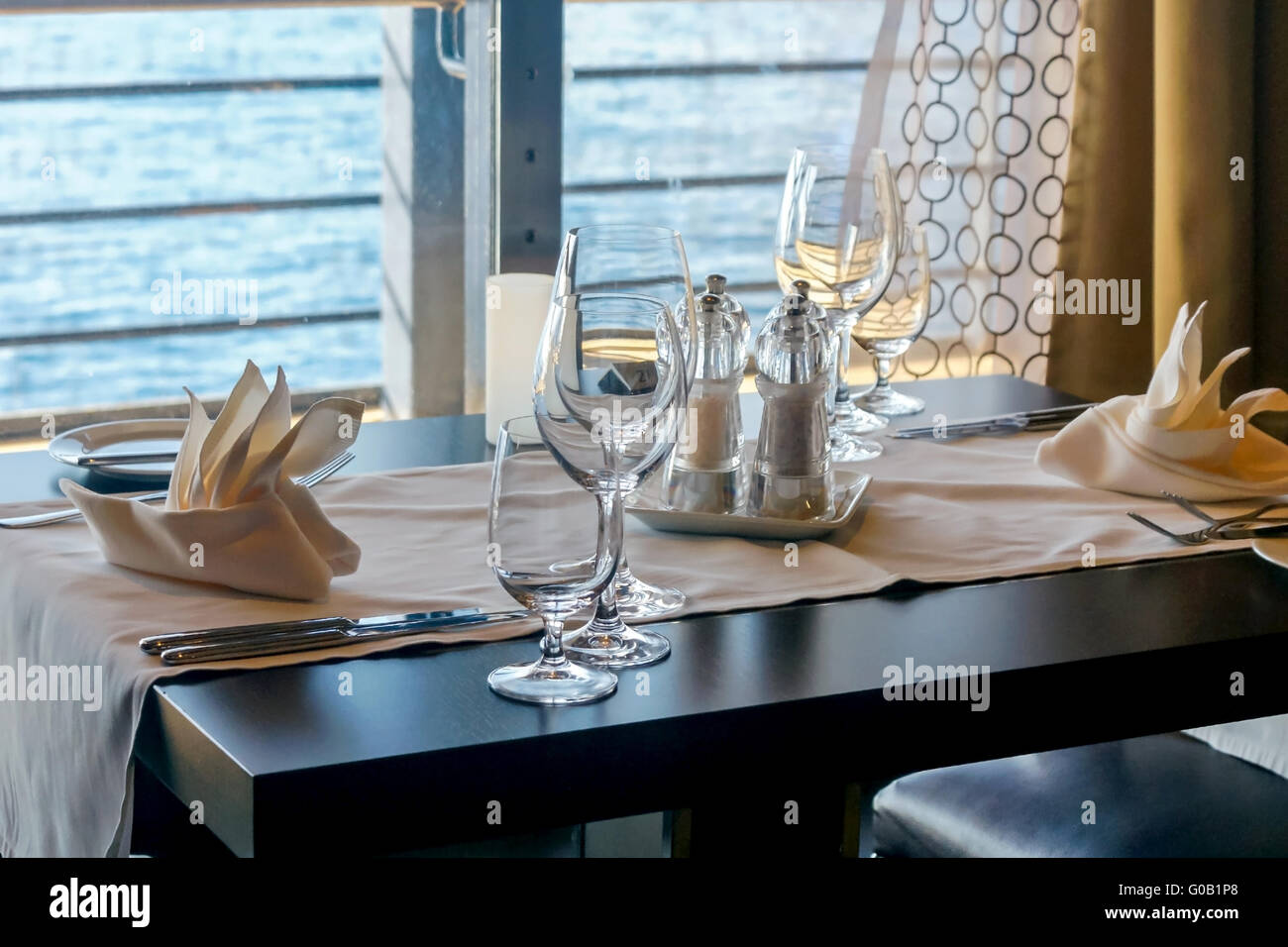 Laid table by the window with ocean in background - Stock Image