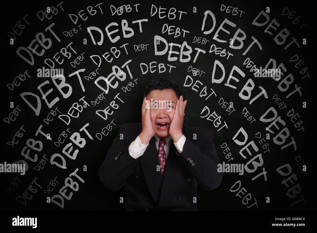 Stress concept, Asian businessman shocked and scream under pressure with debt words on chalk board around him - Stock Image