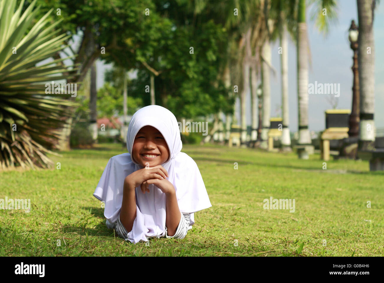 Portrait of happy muslim Asian girl lying down on green grass in the park - Stock Image