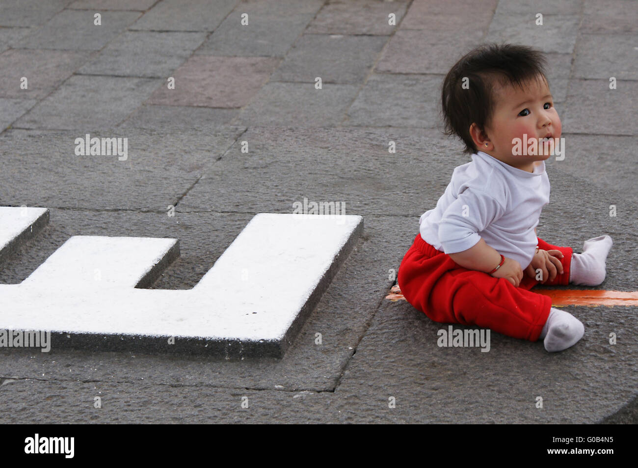 young child sitting on the equator-line, Ecuador - Stock Image