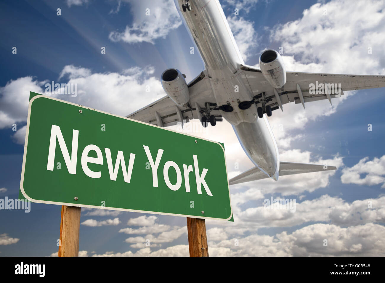 New York Green Road Sign and Airplane Above - Stock Image