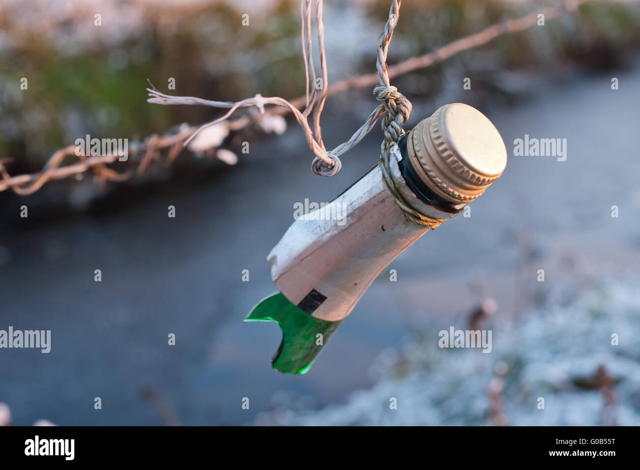 upper part of a broken bottle at a cattle-fence - Stock Image