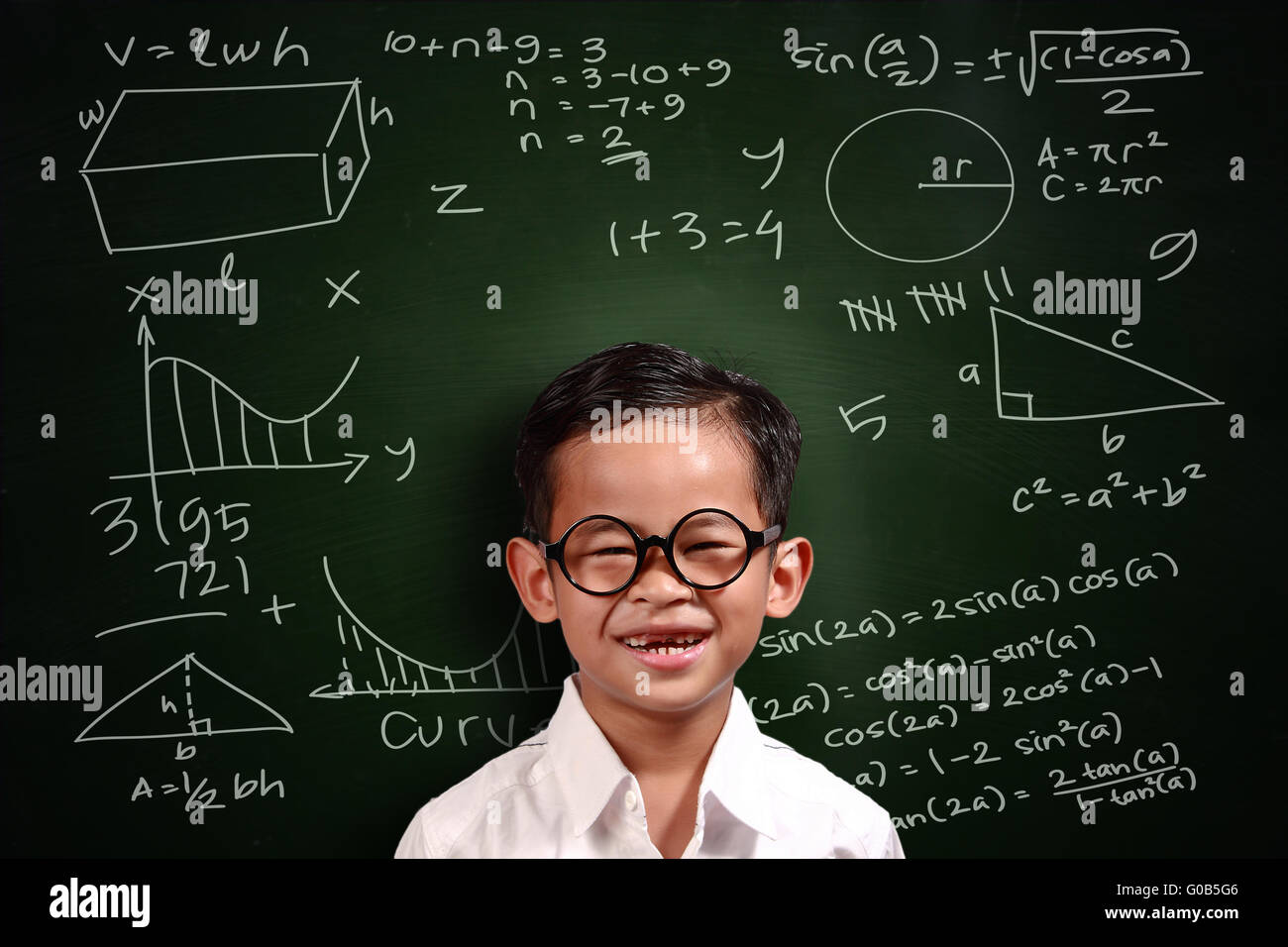Little genius Asian student boy with glasses smiling over green chalkboard with math equivalents written on it - Stock Image