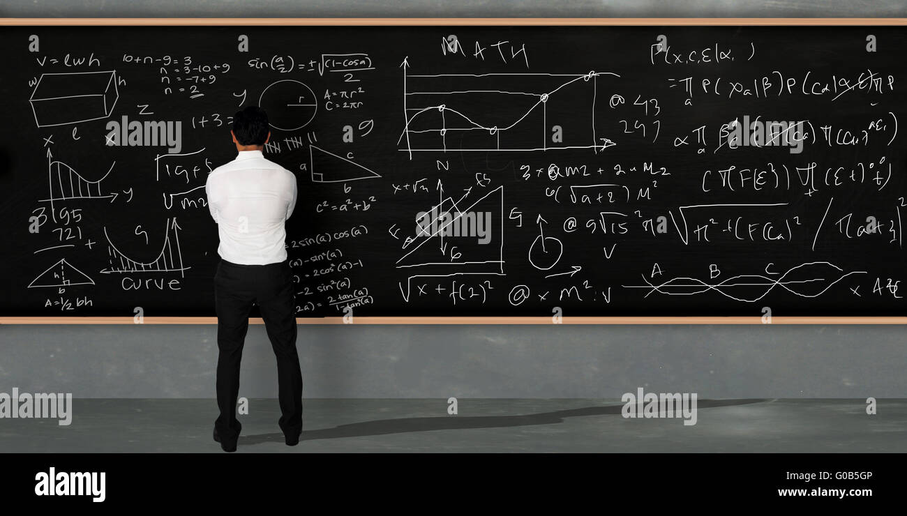 Businessman thinking and standing facing on large blackboard with math equivalents written on it - Stock Image