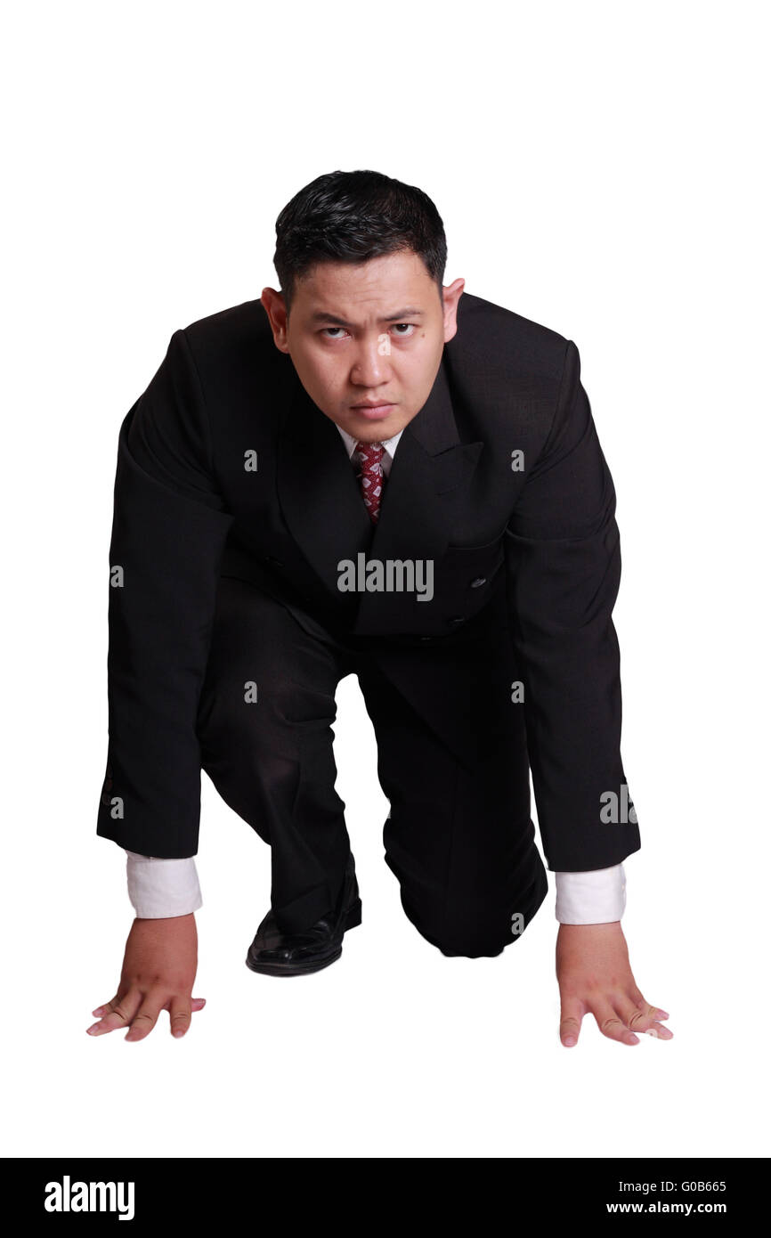 Business concept image of an Asian businessman in start position ready to run - Stock Image