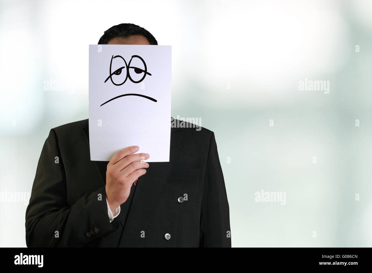 Business concept image of a businessman holding white paper mask with sad and tired face drawn on it - Stock Image