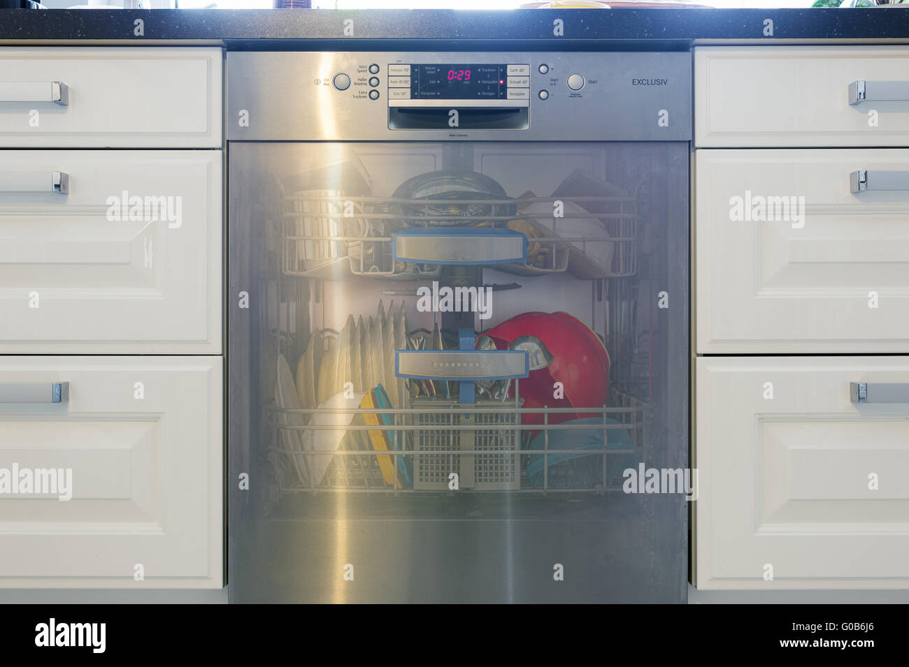 dishwasher filled with transparent flap Stock Photo