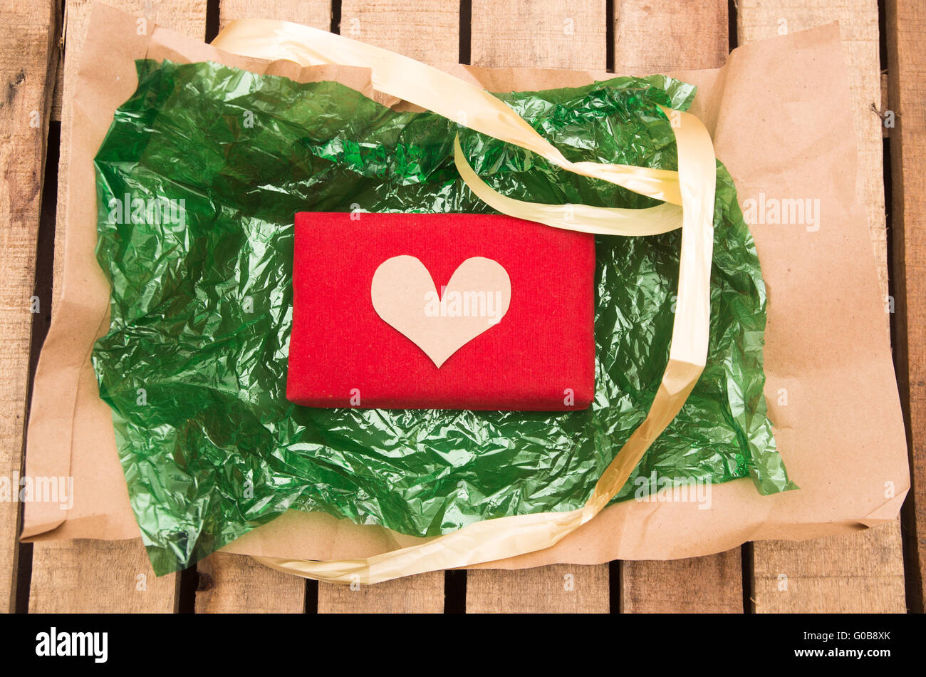 Red present lying on green plastic with golden ribbon string around it, as seen from above Stock Photo