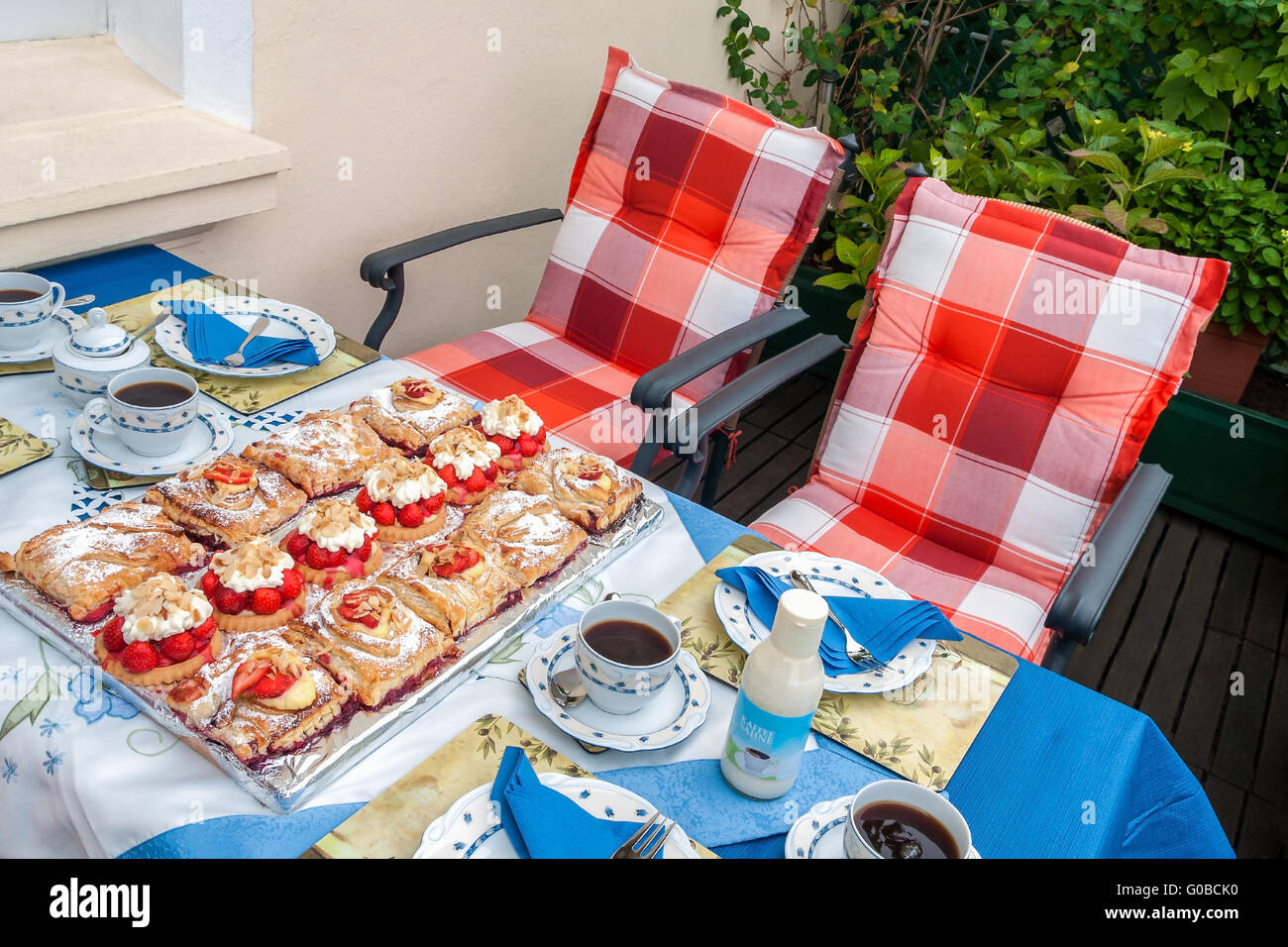 Summerly covered coffee-table with tartes-selectio - Stock Image
