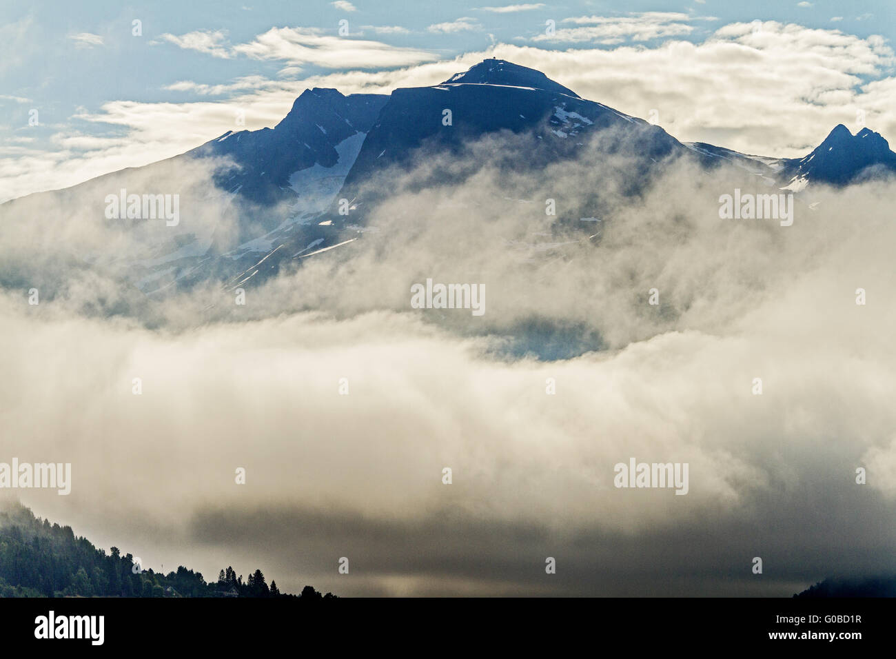 Mountains Poking Through The Clouds Olden Norway - Stock Image
