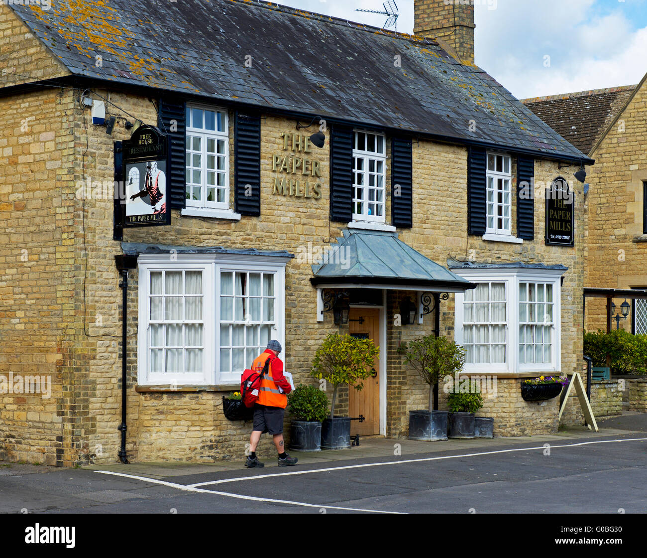 Postman delivering to the Paper Mills pub in the village of Wansford, Cambridgeshire, England UK - Stock Image