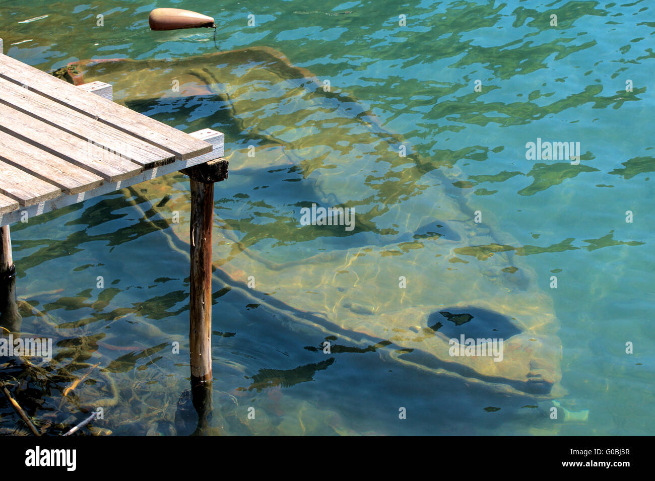 Old rowing boat sunken under water at a wooden jet - Stock Image