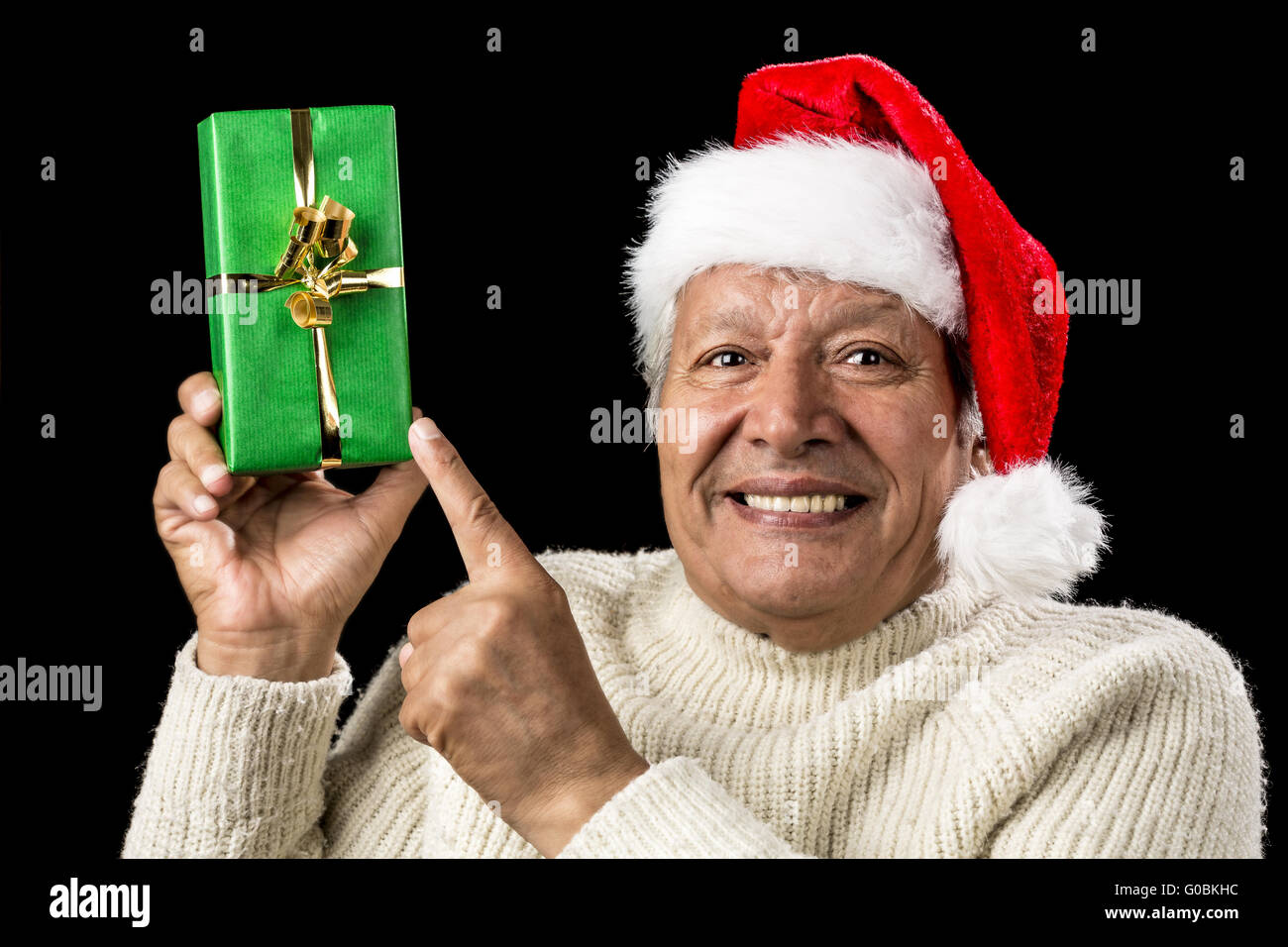 Gleeful Aged Man Pointing At Raised Green Present - Stock Image