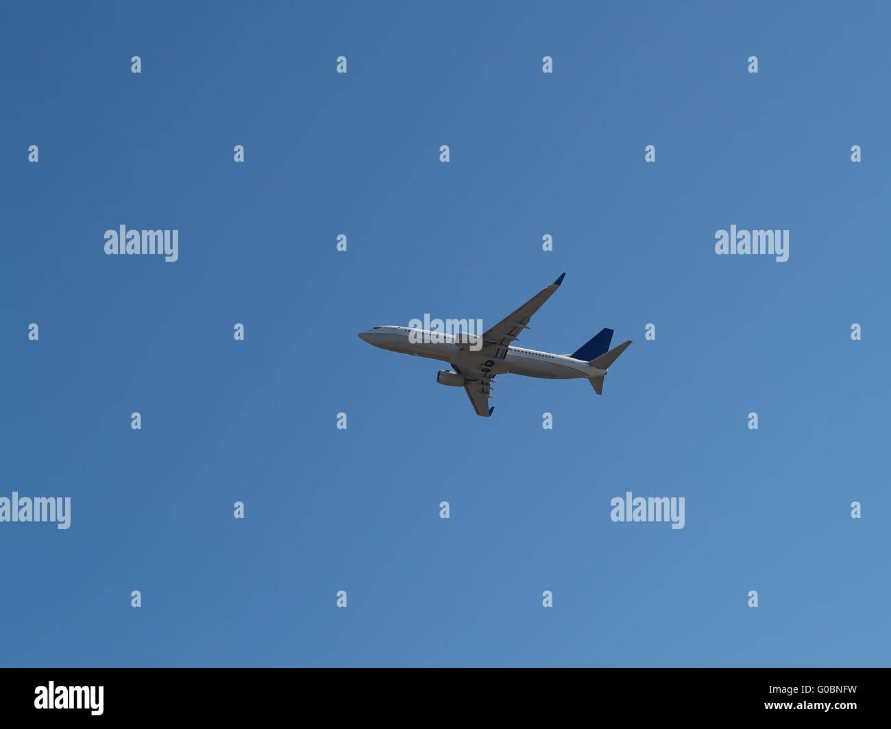 Two Engine Jet Liner Climbing Into Blue Sky - Stock Image
