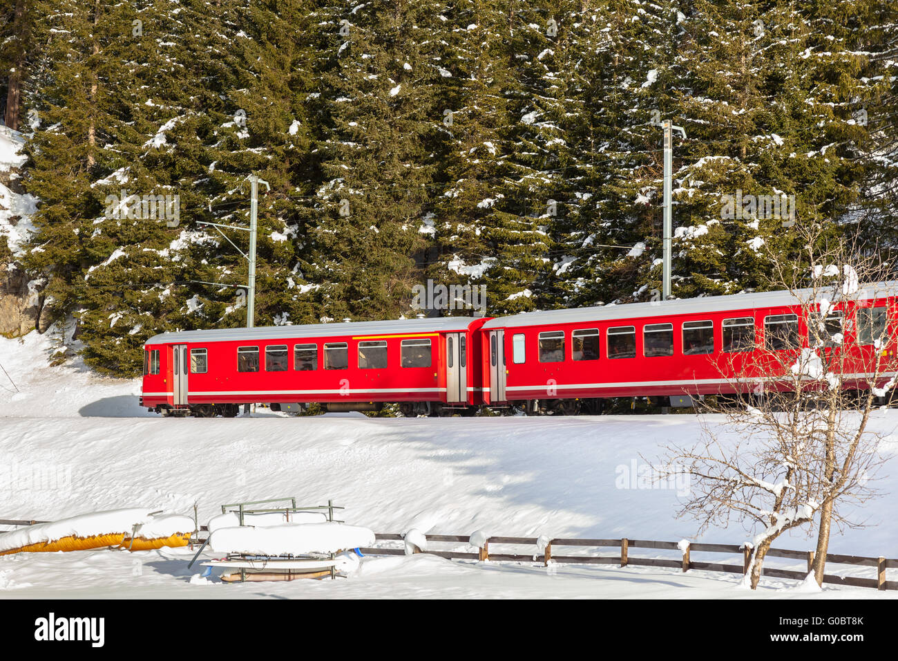 Famous sightseeing train of Rhaetian Railway running in snow, the Glacier Express in winter of Switzerland - Stock Image