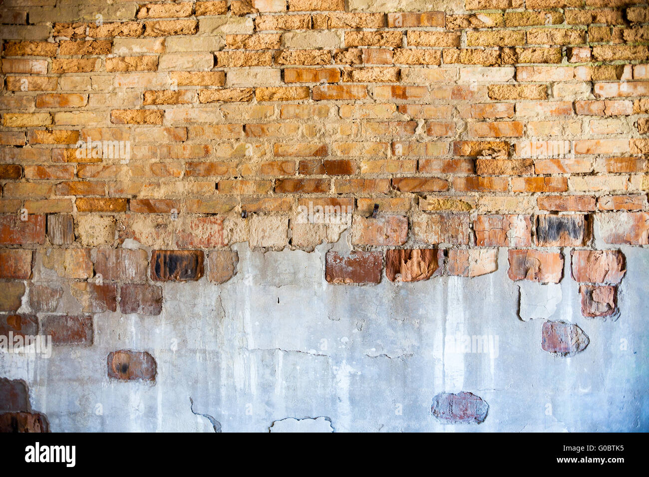 Old brick wall with the damaged plaster Stock Photo
