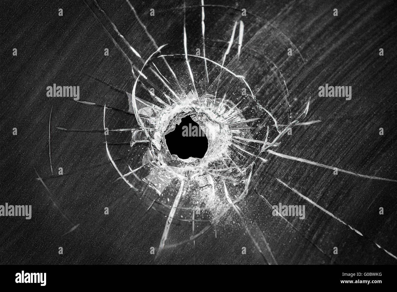 Bullet shot cracked hole on broken window glass - Stock Image