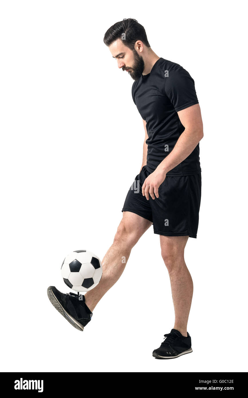 Side view of freestyle soccer or futsal player juggling ball with his legs. Full body length portrait isolated on - Stock Image