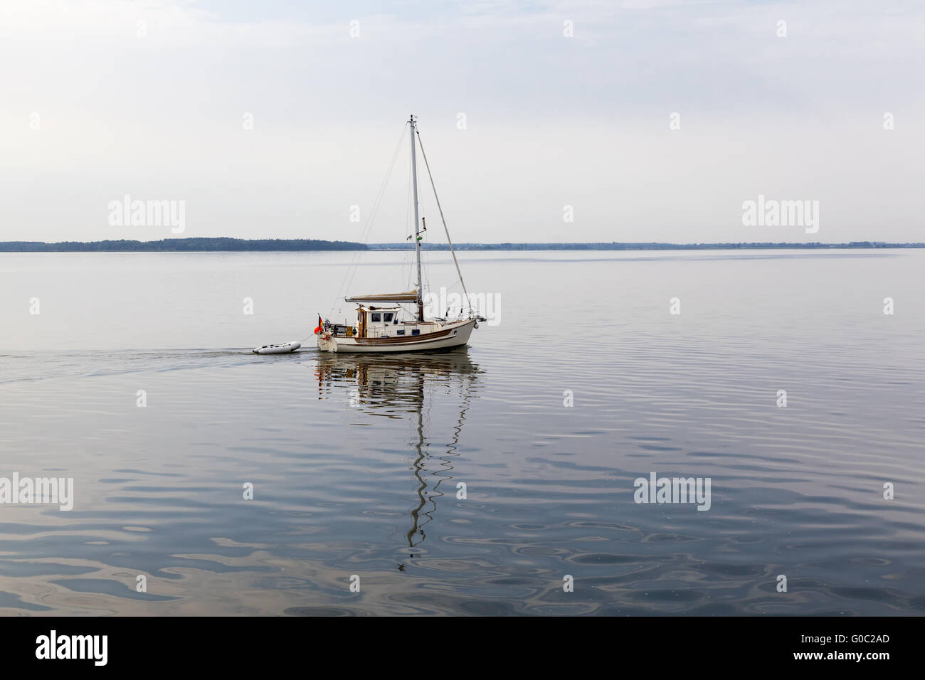 Small sailing boat with reflection on the Bodden - Stock Image